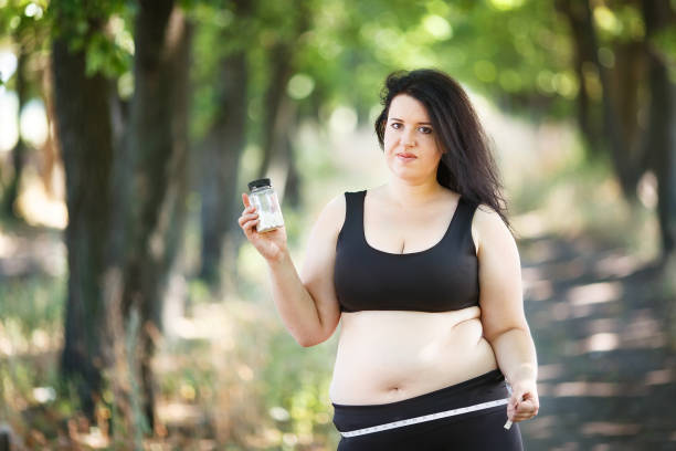 Overweight fat woman with measuring tape and slimming pills. Wei stock photo
