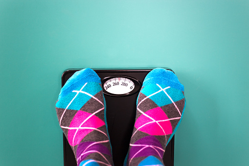istock Overweight: Feet in Colorful Argyle Socks  on Scale 1135634838