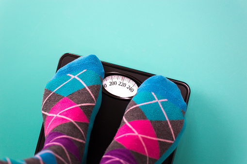 istock Overweight: Feet in Colorful Argyle Socks on Scale 1135634859