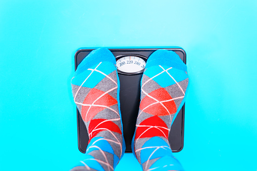 istock Overweight: Feet in Colorful Argyle Socks on Scale 1135634935
