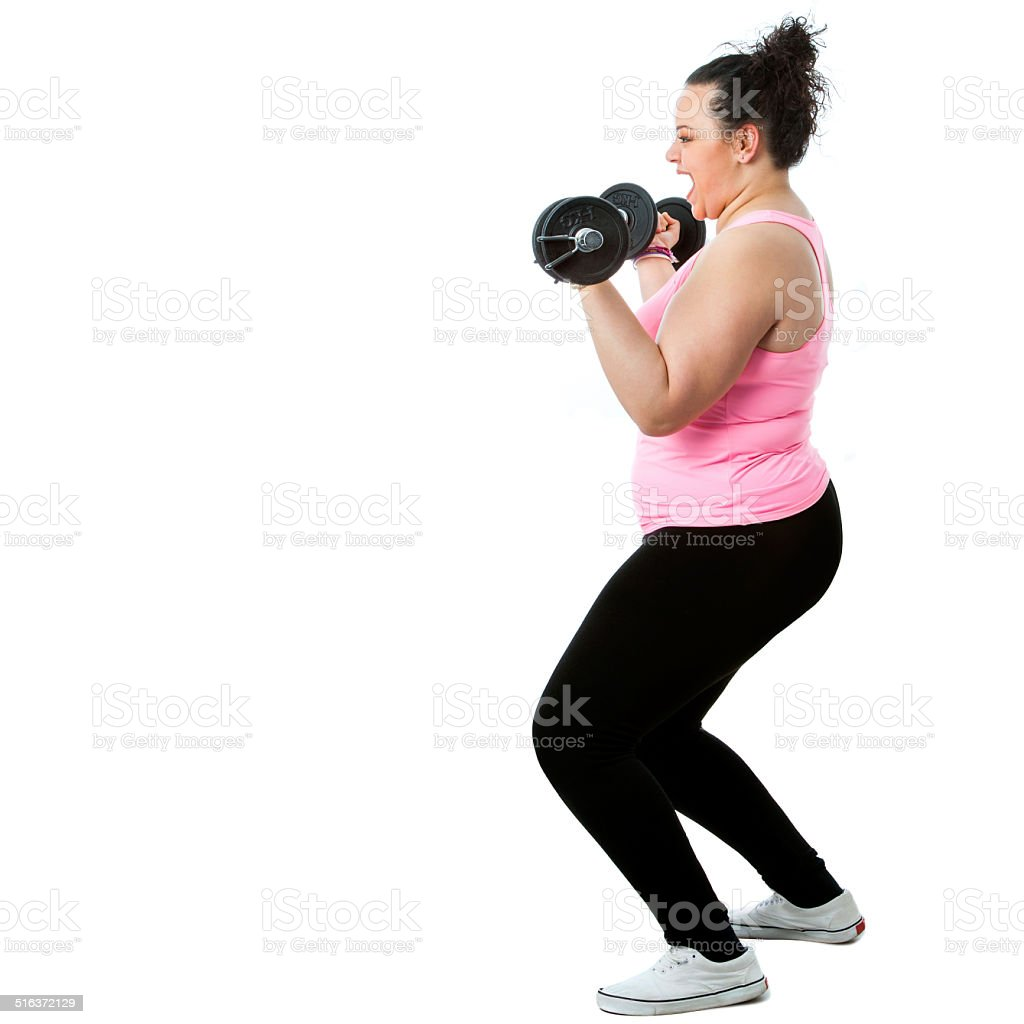 Overweight girl doing workout. Full length portrait of obese girl doing workout with weights.Isolated on white background. Activity Stock Photo