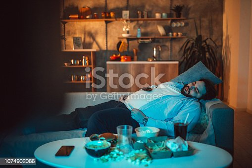 Overweight guy, lying on sofa and napping, with junk food in front of him.