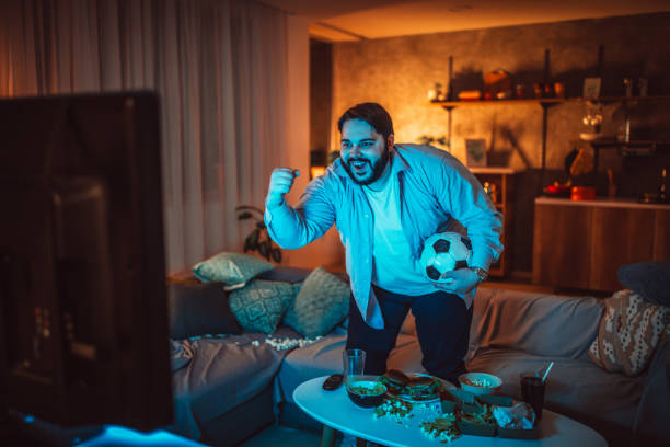 Overweight guy watching a soccer match at home One man, sitting at home, eating burgers and watching a sports match alone. man cave couch stock pictures, royalty-free photos & images