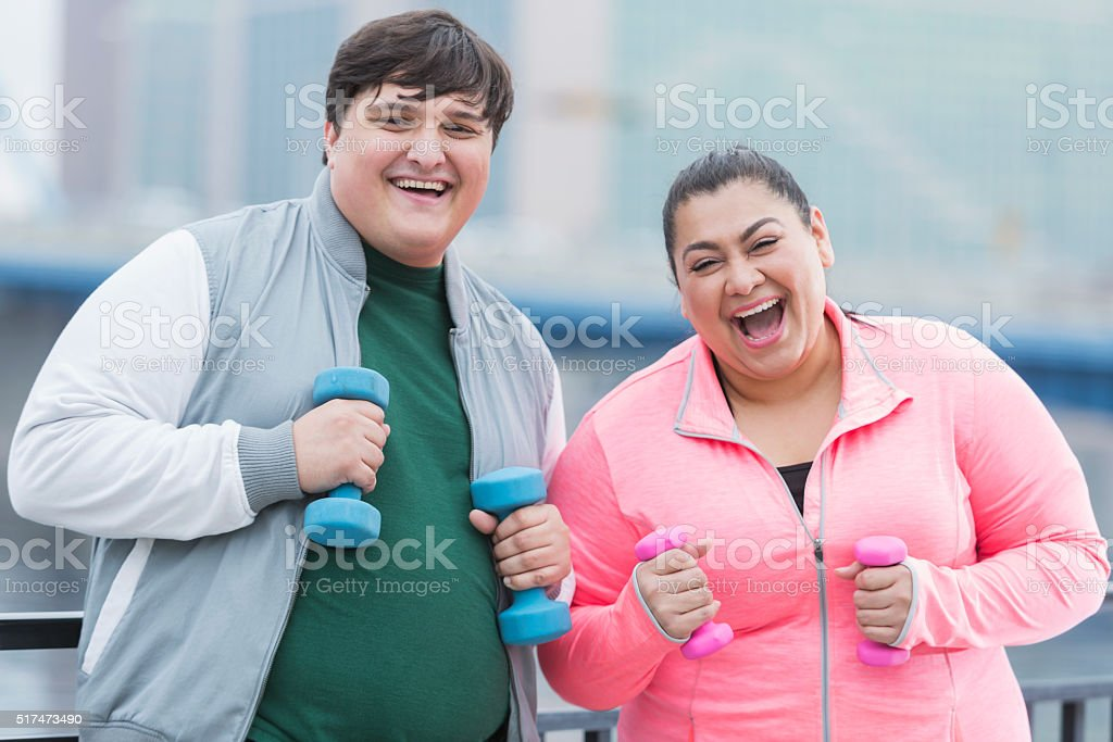 An overweight man and woman exercising together outdoors. They are...