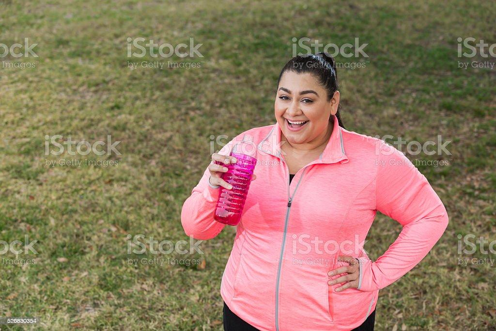 Overweight Hispanic woman exercising, drinking water stock photo
