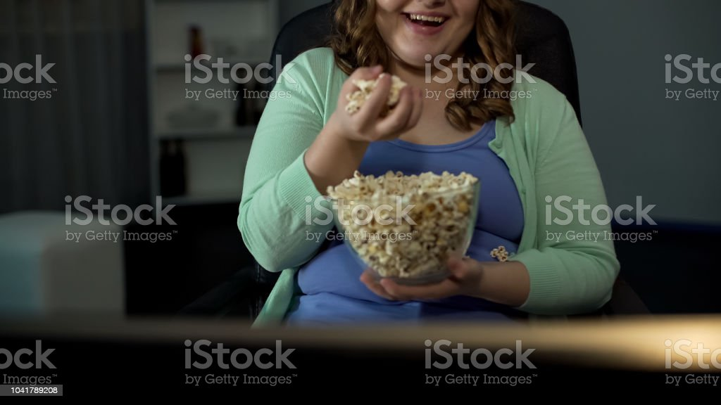 Overweight lady enjoying TV show at home, eating salty popcorn,...