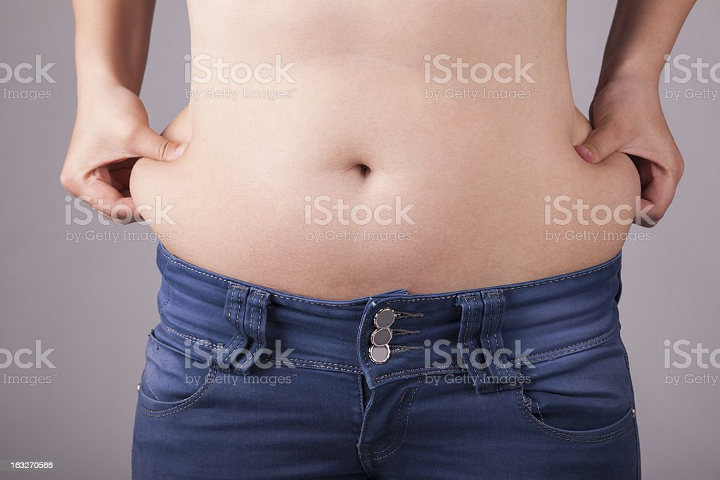 Overweight lady holding fat belly stock photo