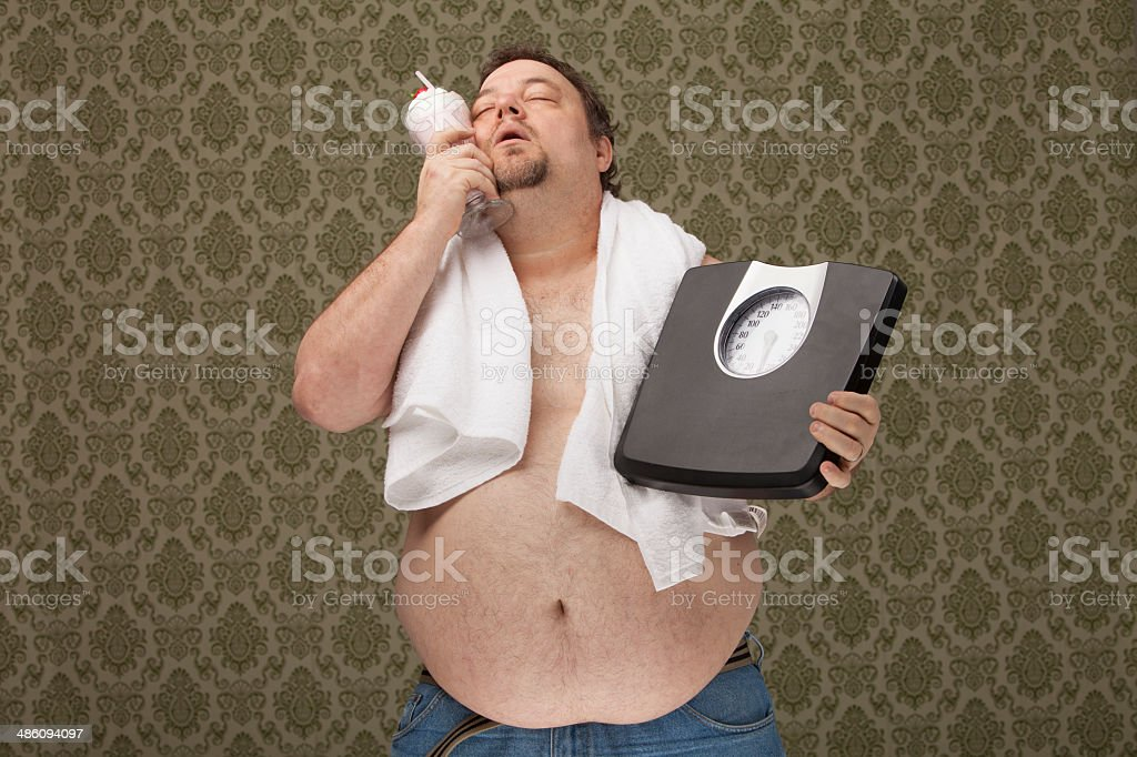 overweight male after workout and holding scales wants to drink stock photo