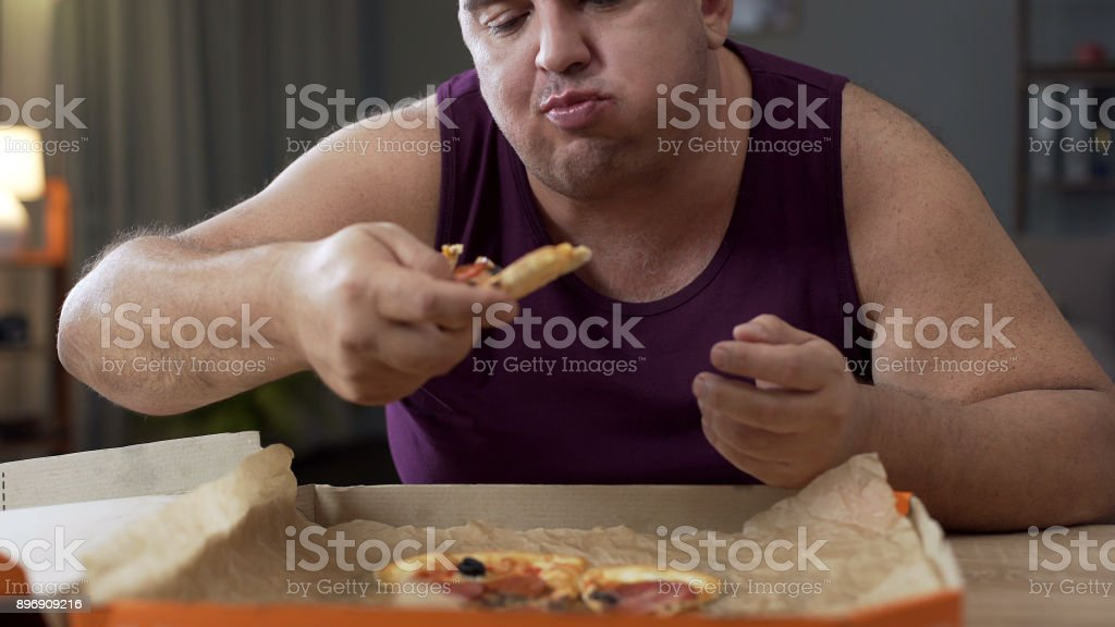 Overweight male eating pizza with delight at night, addiction to unhealthy food stock photo