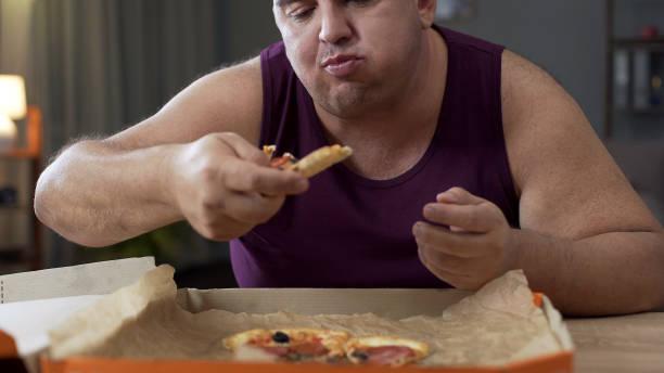 overgewicht mannelijke eten pizza met vreugde in de nacht, verslaving aan ongezonde voeding - dikke pizza close up stockfoto's en -beelden