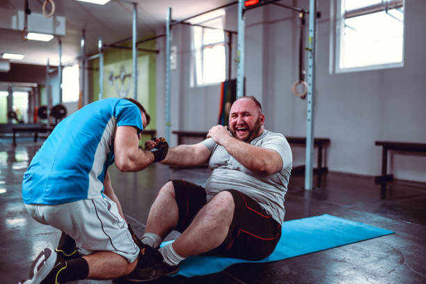 Overweight Male Happy About Gym Improvement Rejoicing With Friend stock photo
