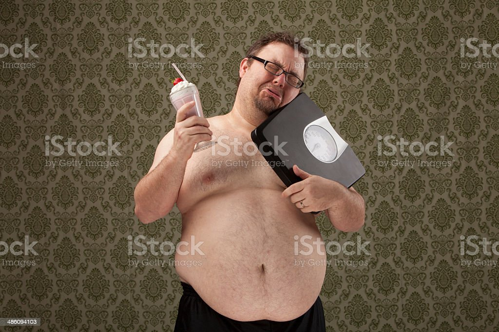 overweight male holding scales and milkshake stock photo