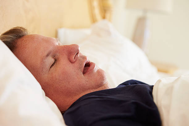 Overweight Man Asleep In Bed Snoring Overweight Man Asleep In Bed Snoring At Home On His Own mouth open stock pictures, royalty-free photos & images