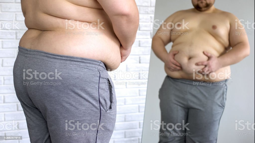 Overweight man checking his fat body reflection in mirror, belly...