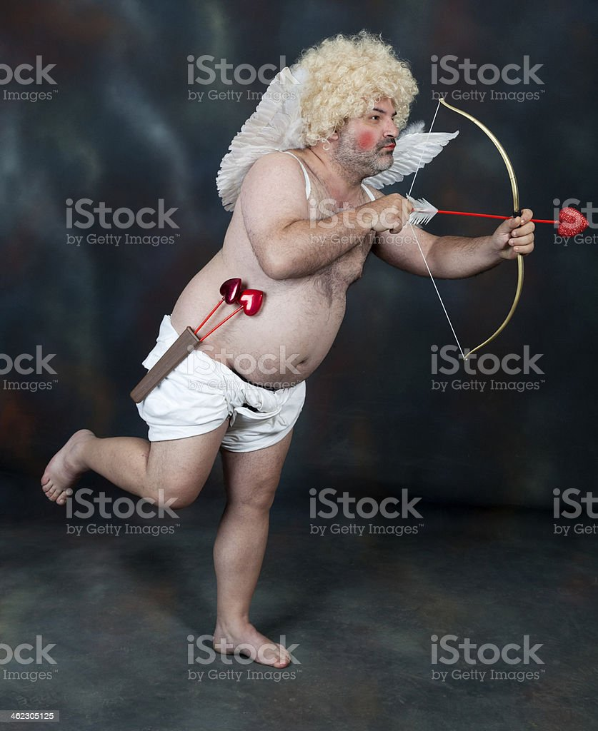 Overweight man dressed as Cupid pointing arrow wearing wig stock photo