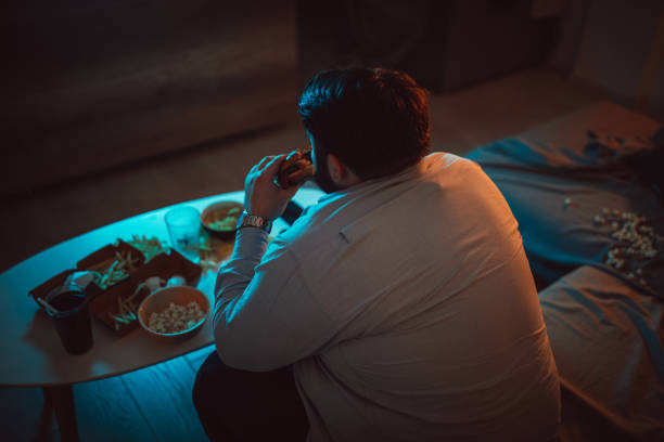overweight man eating a burger - slow food foto e immagini stock
