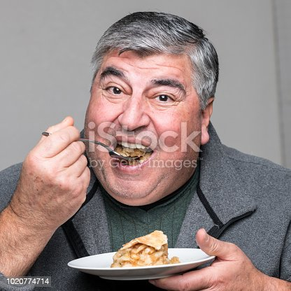 Smiling Overweight man having a piece of apple pie on gray background