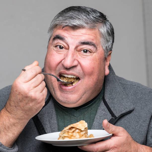 Overweight man having a piece of apple pie stock photo