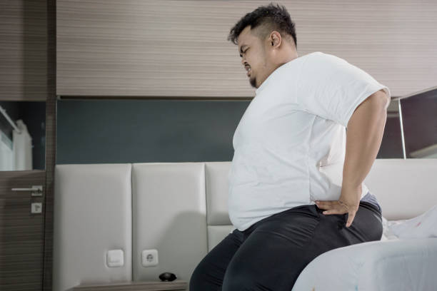 Overweight man having backache on the bed stock photo