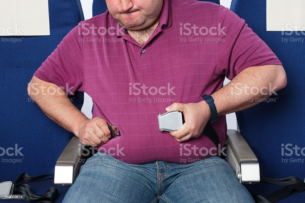 Overweight man in an airplane stock photo