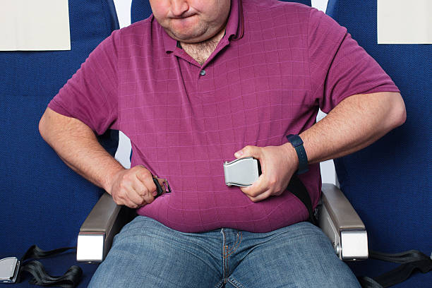 overweight man in an airplane - stomach sitting stock photos and pictures