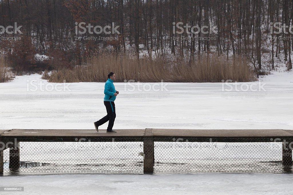 Overweight adult man in tracksuit running on bridge across frozen...