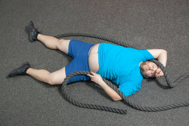 Overweight man is lying on the floor exhausted after performing battle rope exercise in the fitness gym stock photo
