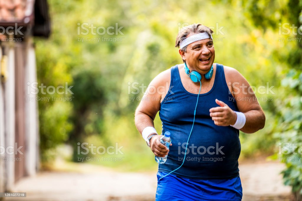Overweight Man Jogging Exercising Doing Cardio In The Park Slightly Overweight Loosing Weight Stock Photo Download Image Now Istock