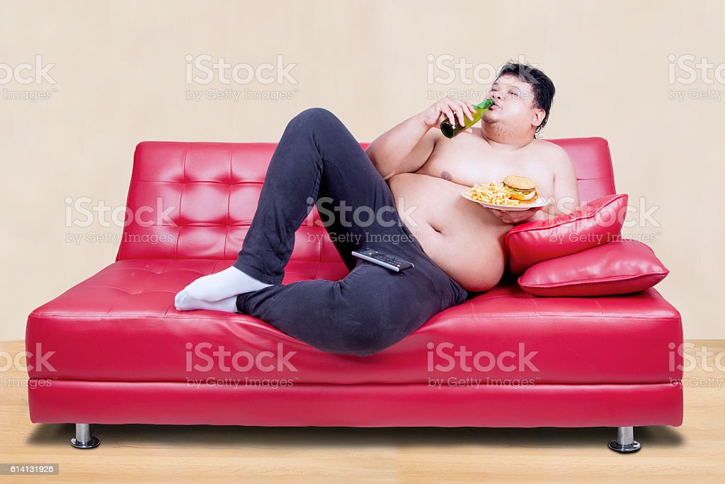 Image of overweight man leaning on the couch while drinking beer and...