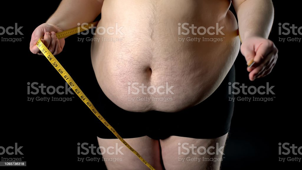 Overweight man measuring belly with tape, weight loss, unhealthy...