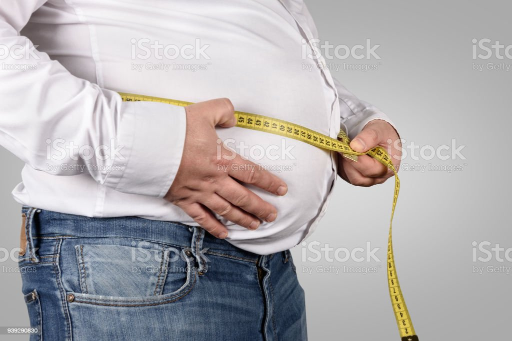 Overweight Man Measuring His Belly with tape measure stock photo