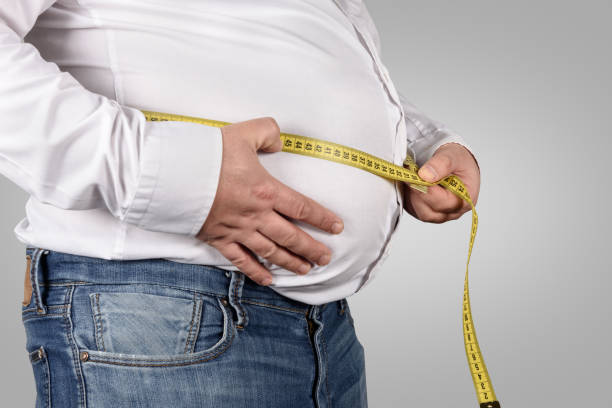 overweight man measuring his belly with tape measure - stomach stock pictures, royalty-free photos & images