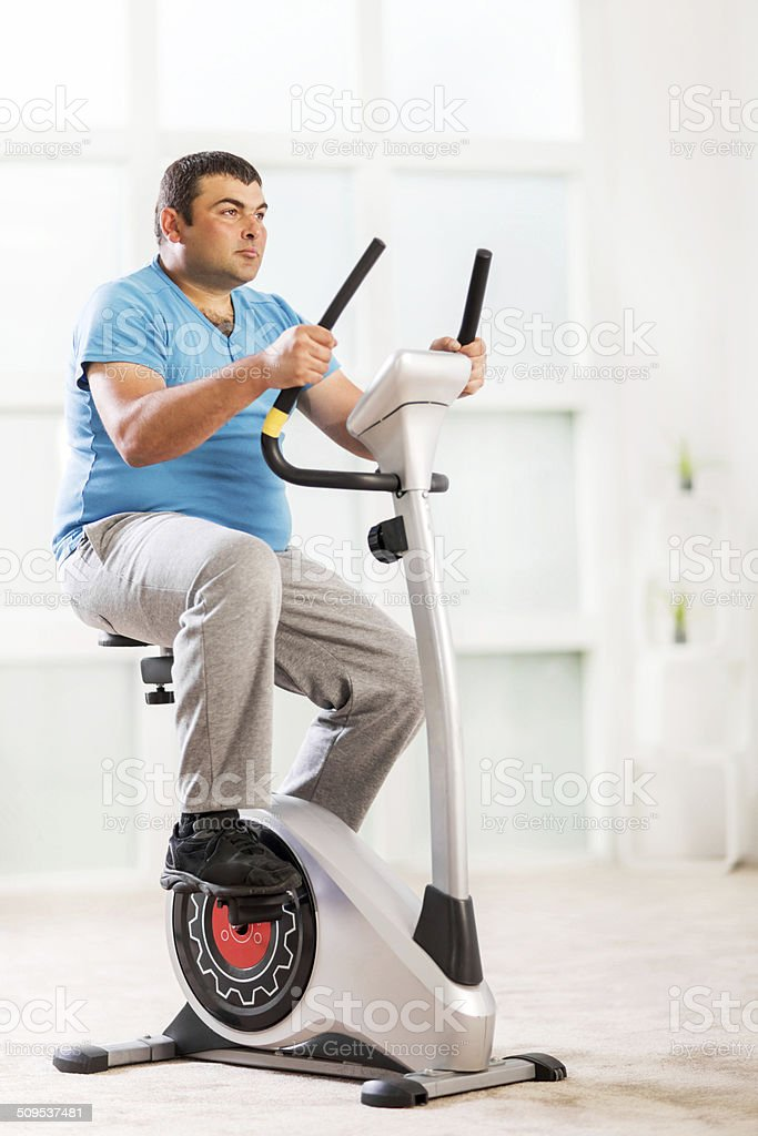 Young overweight man exercising on an exercise bike.