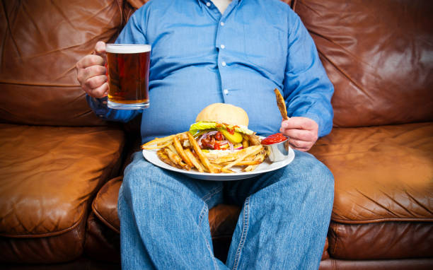 overweight man over-eating on a couch - stomach sitting stock photos and pictures