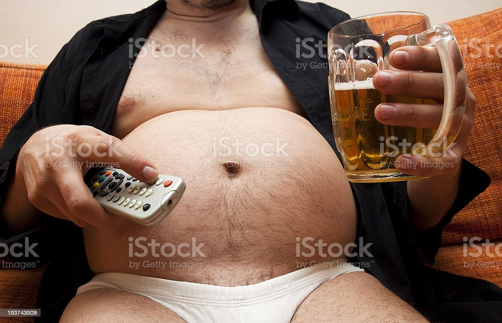 Overweight man sitting on the couch with a beer glass and remote...