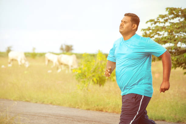 overweight man running on road - concept of fat man fitness - obese person jogging to reduce the weight. - active shooter training stock photos and pictures