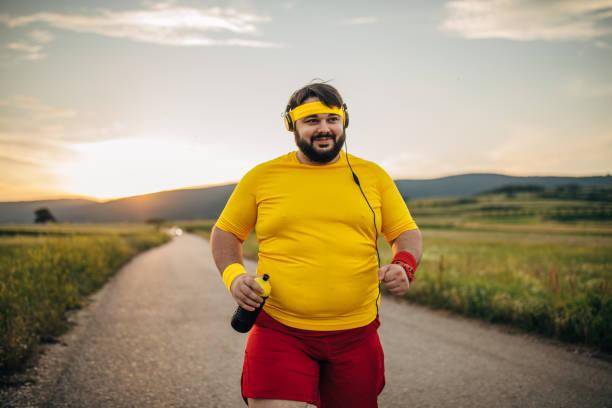 übergewichtiger mann läuft - motivationsmusik stock-fotos und bilder
