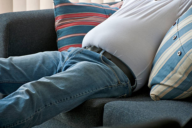 overweight man sat on couch - stomach sitting stock photos and pictures