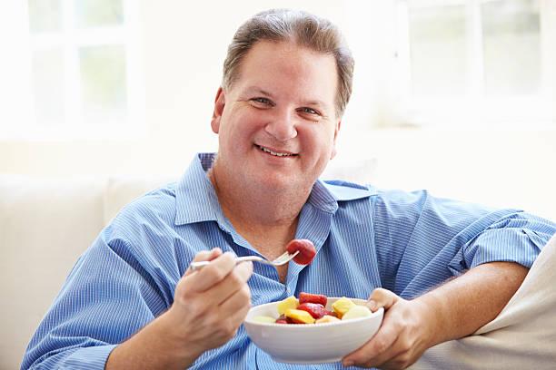 übergewichtige mann sitzt auf der couch essen schale mit frischem obst. - fett nährstoff stock-fotos und bilder