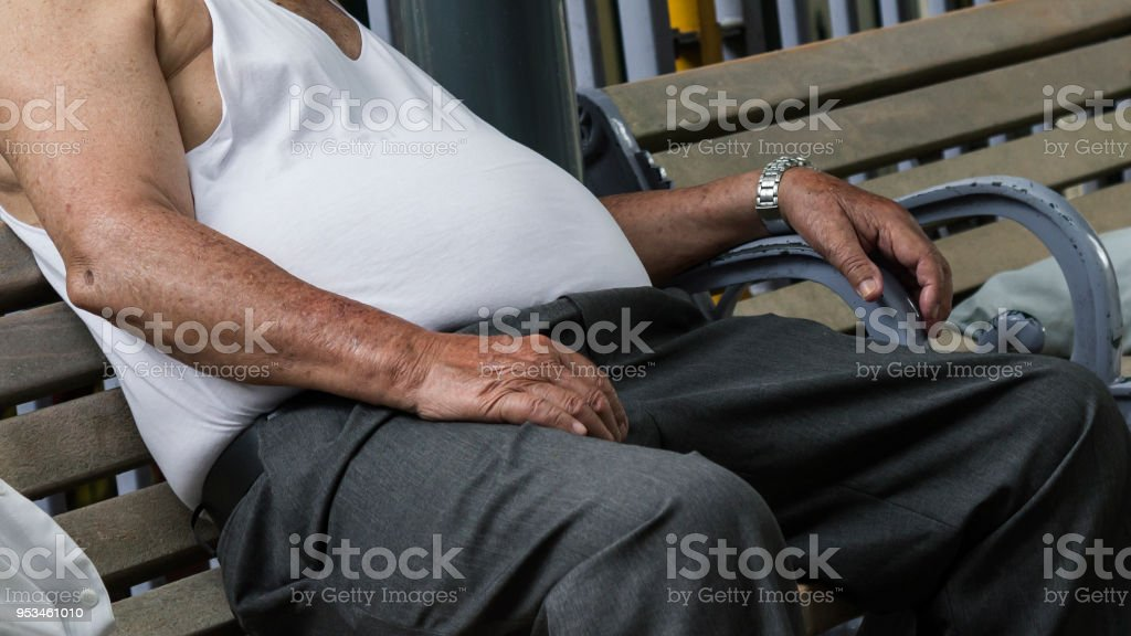 Overweight man sitting slumped on a park bench. stock photo