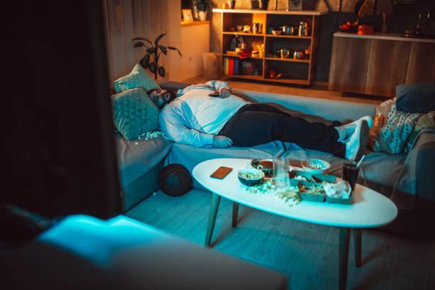 overgewicht man slapen op de bank in een rommelige kamer - lazy stockfoto's en -beelden