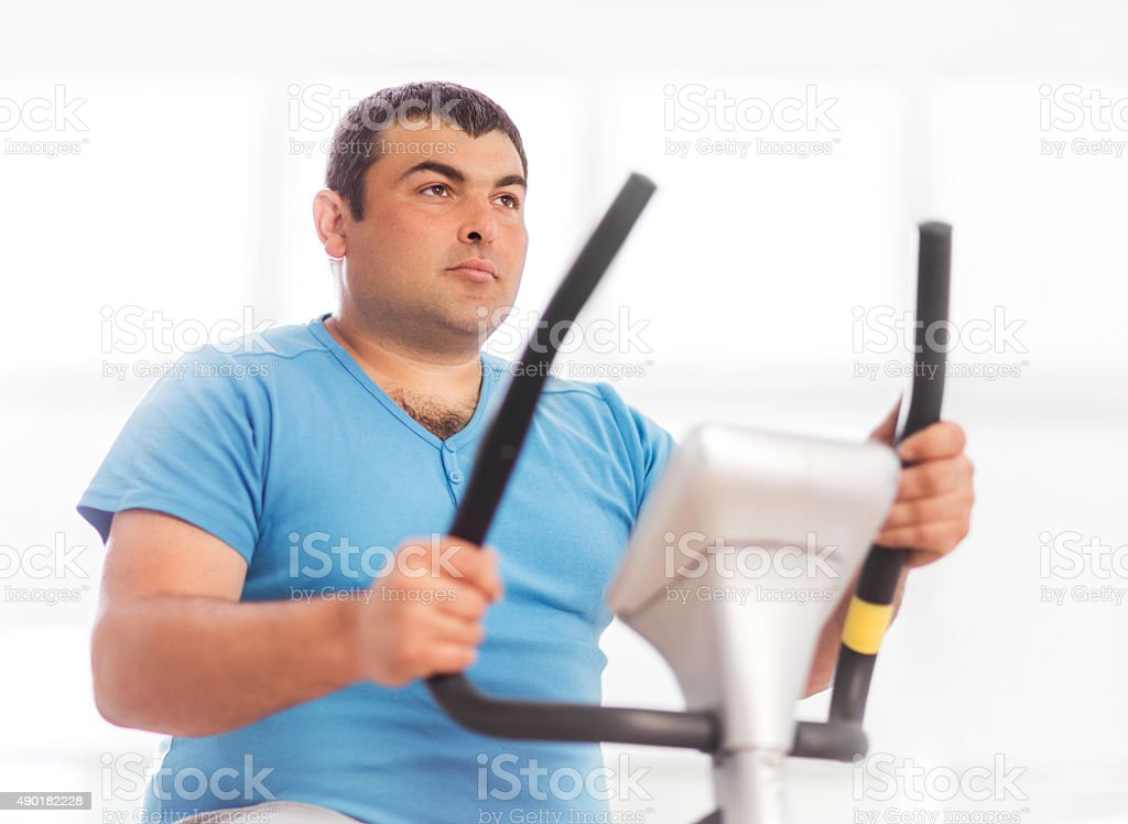 Serious overweight man cycling on exercise bike.