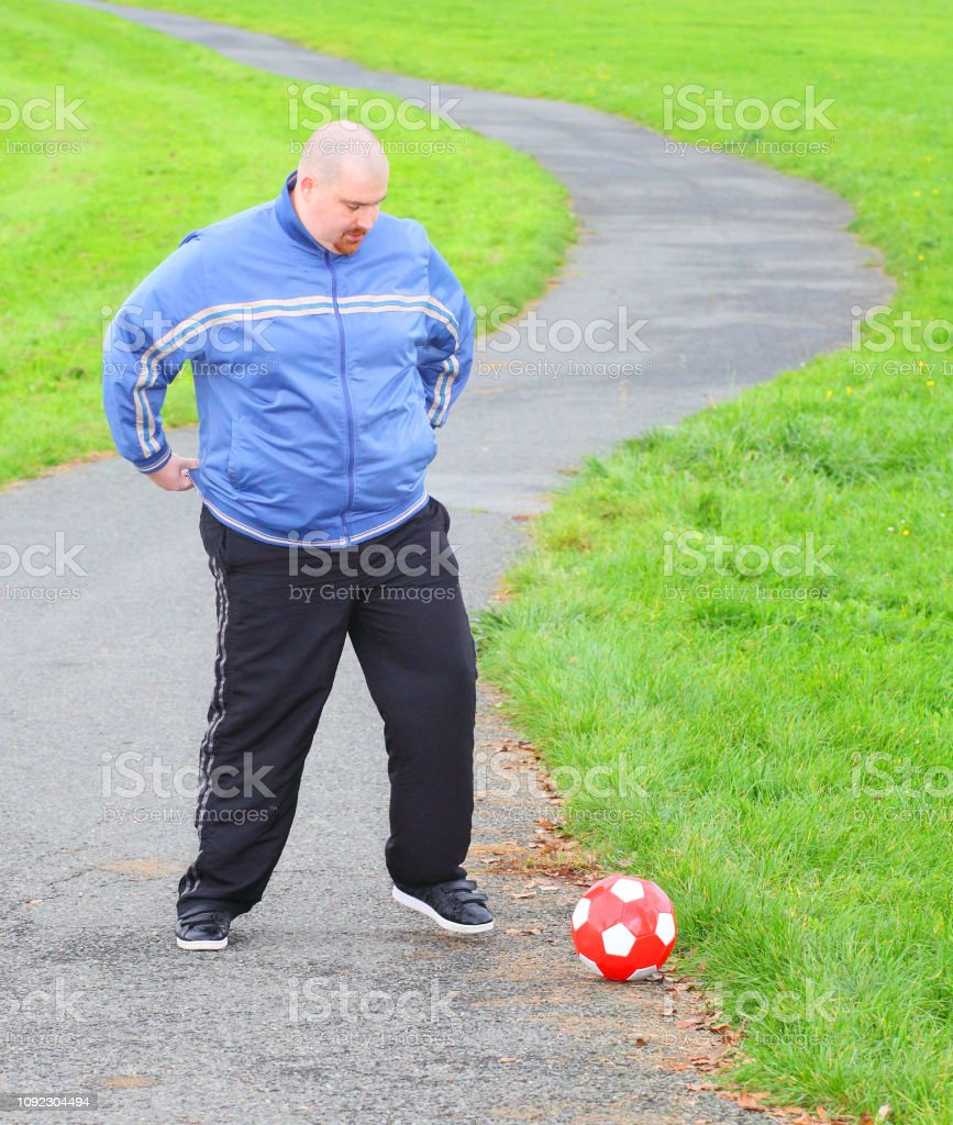 Overweight man training with soccer ball. Weight loss concept.