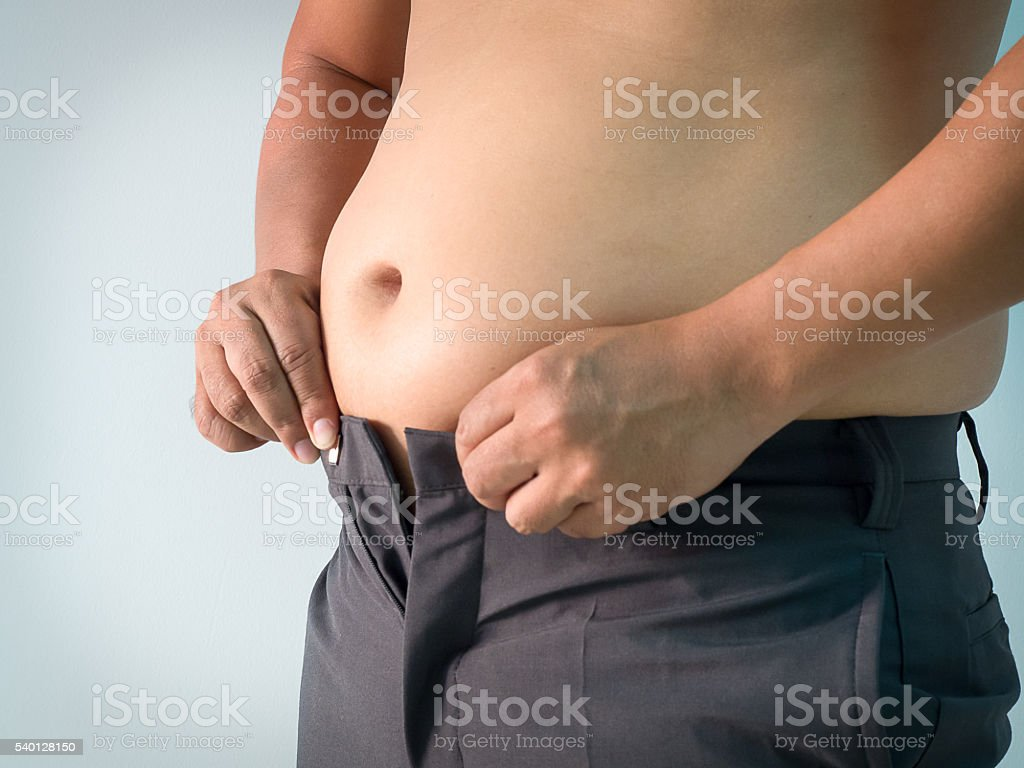 Overweight man trying fasten small pants, fat man big belly. stock photo