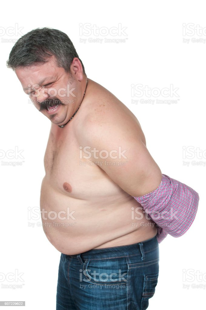Overweight man trying to fasten too small clothes stock photo