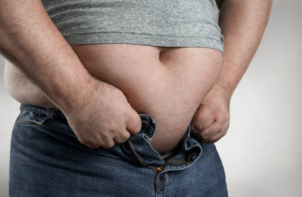 Overweight man trying to wear too small jeans stock photo