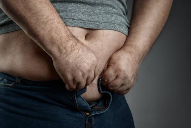 übergewichtige mann versucht, zu kleine jeans zu tragen - ausgefallene mode für mollige stock-fotos und bilder