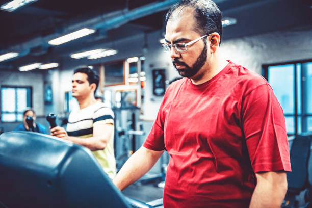 Overweight Man using Treadmill at a Gym stock photo