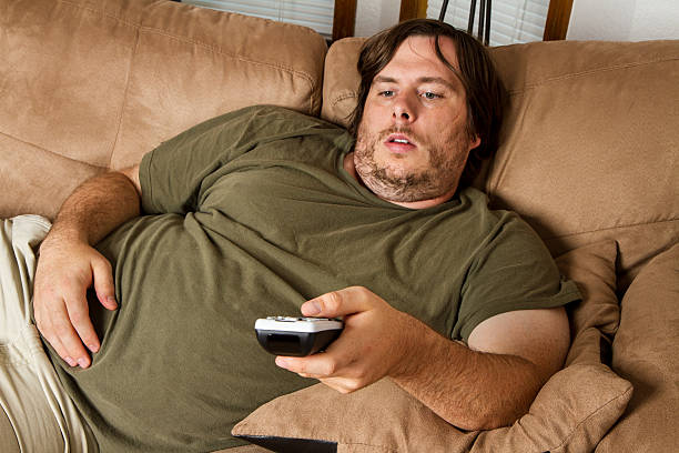 overweight man watching tv on the couch - laziness stock photos and pictures