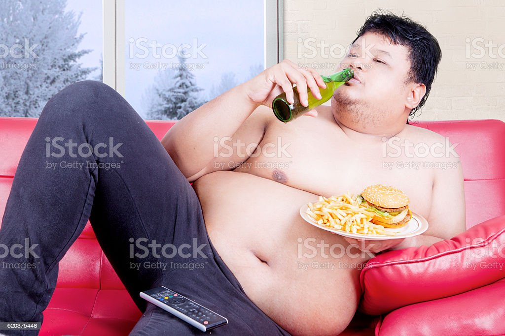 Overweight man with drinks and meals stock photo